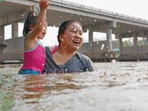 Wenig asiatisches Baby genießt, Wasser in einem Fluss mit ihrer Tante zu spielen lizenzfreie stockfotografie