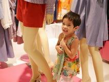 Wenig asiatisches Baby genießt vorzutäuschen, da sie eins der Mannequins ist, die Kleider in einem Einkaufszentrum anzeigen stockfoto
