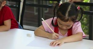 Wenig asiatisches M?dchen, das bewusst irgendeine Karikatur, in Kunstunterricht zeichnet stock video footage