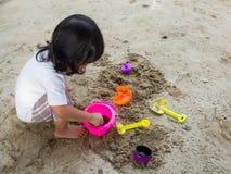 Wenig Asien-Mädchen, das im Sandkasten sitzt und Eimer und sie der Whitspielzeugschaufel spielt, schaufelte im Spielzeugschaufele Stockfoto