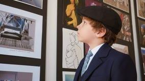 Wenig aufpassendes Bild des Jungen in der Kunstgalerie Junge, der Kunstbild in der kreativen Galerie schaut Moderne malende Kunst stock footage