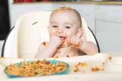 Wenig b, das ihr Abendessen isst und eine Verwirrung macht stockbild
