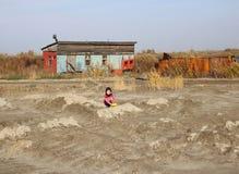 Wenig Baby, das allein auf der Straße nahe dem Haus im Sand spielt lizenzfreies stockbild