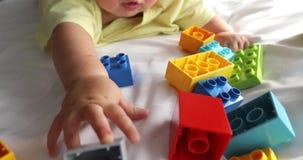 Wenig Baby, das auf wei?em Leinen zwischen Spielwaren liegt stock video footage