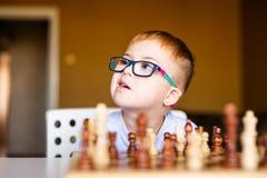 Wenig Baby mit Down-Syndrom mit den großen blauen Gläsern, die Schach im Kindergarten spielen stockfotografie