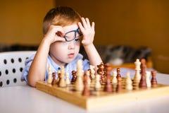 Wenig Baby mit Down-Syndrom mit den großen blauen Gläsern, die Schach im Kindergarten spielen stockbilder