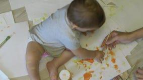 Wenig Baby zeichnet Farben auf Papier in der Zeitlupe stock video footage