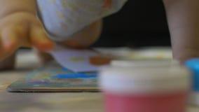 Wenig Baby zeichnet Farben auf Papier in der Zeitlupe stock footage