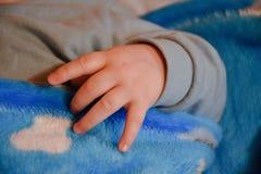 Wenig Babyhand auf blauer Decke lizenzfreie stockbilder