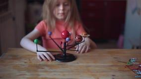 Wenig blonde Mädchenspiele mit dem Plan des Sonnensystems stock footage