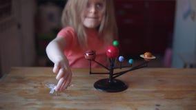 Wenig blonde Mädchenspiele mit dem Plan des Sonnensystems stock video
