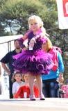 Wenig blonder Engel im purpurroten Kleid am Schönheitswettbewerb Stockbild