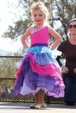 Wenig blonder Engel im Regenbogenkleid am Schönheitswettbewerb Stockfoto