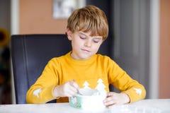 Wenig blonder Kinderjunge mit den gelockten Haaren Eiscreme zu Hause essend oder im Kindergarten Schönes Kind mit großem Eiscreme stockbild