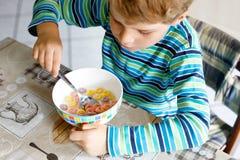 Wenig blonder Schulkinderjunge, der Getreide mit Milch und Beeren, frische Erdbeere zum Frühstück isst Lizenzfreies Stockfoto