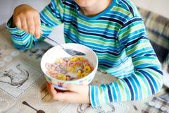 Wenig blonder Schulkinderjunge, der Getreide mit Milch und Beeren, frische Erdbeere zum Frühstück isst Stockbild