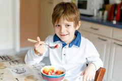 Wenig blonder Schulkinderjunge, der Getreide mit Milch und Beeren, frische Erdbeere zum Frühstück isst Lizenzfreie Stockfotografie