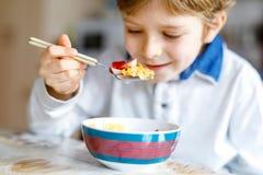 Wenig blonder Schulkinderjunge, der Getreide mit Milch und Beeren, frische Erdbeere zum Frühstück isst Stockbilder
