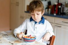 Wenig blonder Schulkinderjunge, der Getreide mit Milch und Beeren, frische Erdbeere zum Frühstück isst Lizenzfreies Stockbild