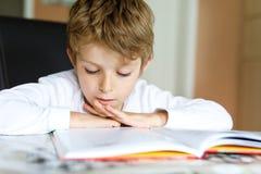 Wenig blonder Schulkinderjunge, der zu Hause ein Buch liest Stockbilder