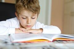 Wenig blonder Schulkinderjunge, der zu Hause ein Buch liest Stockfotografie