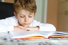 Wenig blonder Schulkinderjunge, der zu Hause ein Buch liest Lizenzfreie Stockfotos