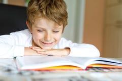 Wenig blonder Schulkinderjunge, der zu Hause ein Buch liest Stockbild