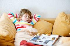 Wenig blonder Schulkinderjunge mit Gläsern ein Buch zu Hause lesend Stockfoto
