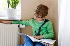 Wenig blonder Schulkinderjunge mit Gläsern ein Buch zu Hause lesend Lizenzfreies Stockfoto