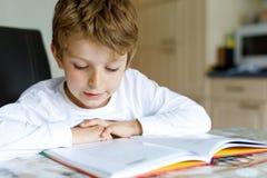 Wenig blonder Schulkinderjunge mit Gläsern ein Buch zu Hause lesend Lizenzfreies Stockbild