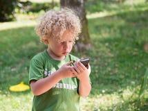 Wenig blonder und gelockter Junge, der mit einem Handy, im Freien spielt Lizenzfreie Stockfotografie