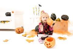 Wenig blondes Kurvenmädchen mit dem Pumking in Halloween-Dekoration Lizenzfreies Stockbild