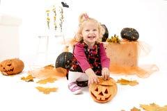 Wenig blondes Kurvenmädchen mit dem Pumking in Halloween-Dekoration Lizenzfreie Stockfotos