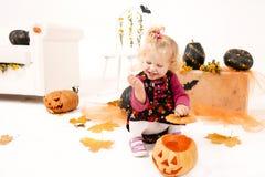 Wenig blondes Kurvenmädchen mit dem Pumking in Halloween-Dekoration Lizenzfreie Stockfotografie