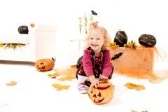 Wenig blondes Kurvenmädchen mit dem Pumking in Halloween-Dekoration Stockfoto