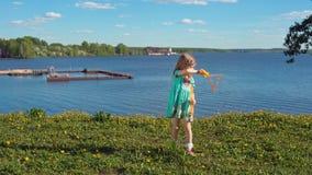 Wenig blondes Mädchen bläst große Seifenblasen gegen Hintergrund der Seeküste auf stock video footage