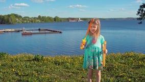 Wenig blondes Mädchen bläst große Seifenblasen gegen Hintergrund der Seeküste auf stock footage