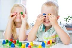 wenig blondes Mädchen und Junge haben Spaß, lachen und geben sich das Spielen des Brettspiels hin Griffleutezahlen in den Händen  stockfotos