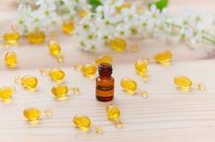 Wenig braune Flasche mit neroli ätherischen Ölen, Goldkapseln der natürlichen Kosmetik und Blumen blühen auf dem hölzernen Stockbilder