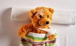 Wenig brauner Teddybär, der in einem Krankenhausbett liegt stockfotografie