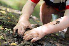 Wenig Child& x27; s-Hände, die in den Schlamm graben lizenzfreies stockbild