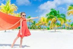 Wenig cutie Mädchen, das Superhelden an einem tropischen Strand spielt lizenzfreie stockbilder