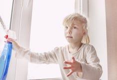 Wenig, das in den weißen Spitzen- und blauen Gamaschen stehen im Raum blond ist, besprüht auf dem Fenster, eine Abhilfe Stockfotografie