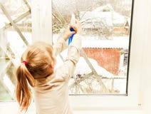Wenig, das in den weißen Spitzen- und blauen Gamaschen stehen im Raum blond ist, besprüht auf dem Fenster, eine Abhilfe Lizenzfreie Stockbilder
