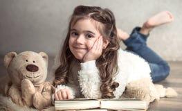 Wenig das Mädchen, das ein Buch mit einem Teddybären liest, betreffen den Boden, Konzept des Entspannung und Freundschaft lizenzfreie stockfotos