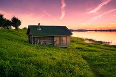 Wenig einziges Haus auf Banken des Flusses bei Sonnenuntergang in der Ruhe Lizenzfreie Stockfotografie