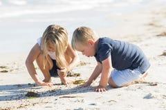 Wenig entzückende und süße Geschwister, die zusammen im Sandstrand mit dem kleinen Bruderumarmen und schöner blonder junger Schwe Lizenzfreie Stockfotos