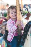 Wenig entzückendes lächelndes Mädchen, das ein Pferd auf Karussellkarussell am Funfair reitet stockbild