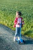 Wenig entzückendes Mädchen, das den Spaß fährt auf Roller hat lizenzfreies stockbild