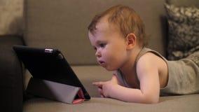 Wenig ernst und einsames Kindmädchen, das auf Tablettenlaptop sitzt und schaut